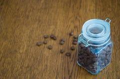 Uma caixa do café na tabela e nos feijões de café dispersados ao redor Imagens de Stock