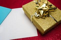 Uma caixa do ouro com curva e cartão Imagens de Stock