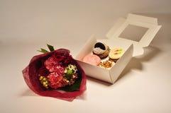 Uma caixa dos queques com flores Imagens de Stock