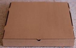 Uma caixa fechado da pizza na tabela Imagens de Stock Royalty Free