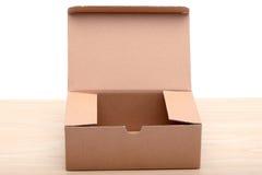 Uma caixa marrom do pacote na placa de madeira no blackground branco Imagens de Stock Royalty Free