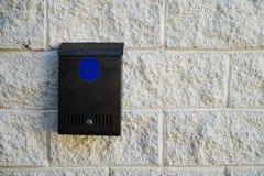 Uma caixa postal do metal com uma etiqueta azul vazia está pendurando na parede de uma casa rural imagens de stock