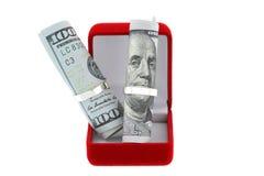 Uma caixa vermelha do anel de veludo com anéis brilhantes e dólar americano Fotos de Stock Royalty Free