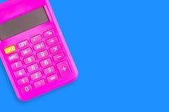 Uma calculadora plástica cor-de-rosa digital na tabela azul no escritório copie o espaço para seu texto Vista superior fotografia de stock