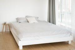 Uma cama de madeira perto da janela Hugge furniture imagem de stock