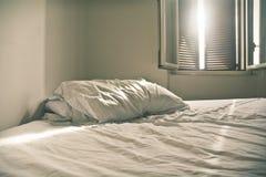 Uma cama desfeita com folhas brancas num domingo à tarde imagem de stock