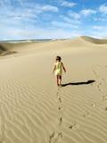 Uma caminhada da menina e pegadas das folhas na duna de areia do deserto Fotos de Stock