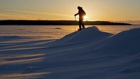 Uma caminhada do sapato de neve do por do sol em um lago congelado fotografia de stock royalty free