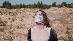 Uma caminhada na roupa suja e rasgada está andando no deserto com uma atadura em sua boca filme