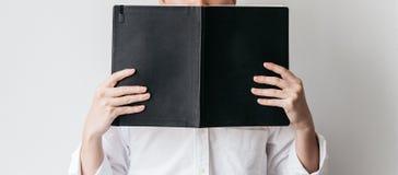Uma camisa branca vestindo do homem e guardar um livro preto da tampa na frente dele fotos de stock