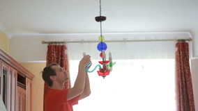 Uma camisa considerável do homem muda uma ampola a uma lâmpada de cristal vídeos de arquivo
