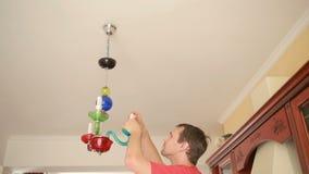 Uma camisa considerável do homem muda uma ampola a uma lâmpada de cristal video estoque