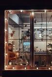 Uma camiseta vestindo da menina bonita que guarda uma lanterna da vela ao sentar-se em um peitoril da janela dentro do café fotografia de stock royalty free