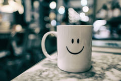 Uma caneca com a cara do smiley com bonito boken e borrou o backgrou Foto de Stock