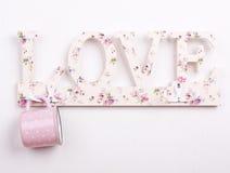 uma caneca cor-de-rosa do às bolinhas com cair do amor Imagem de Stock