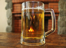 Uma caneca de cerveja em uma tabela de madeira Fotos de Stock Royalty Free