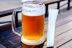 Uma caneca de cerveja fria, gotas misted rola para baixo o vidro Na tabela ao lado do suporte do guardanapo com guardanapo foto de stock