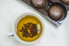 Uma caneca de chá com sobremesa do chocolate em uma tabela clara imagem de stock