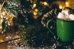 Uma caneca velha do verde do vintage com cacau e marshmallows no fundo das luzes de Natal na superfície de madeira Fotografia de Stock