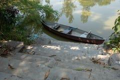 Uma canoa na parte inferior da família mesma próprios ghats imagens de stock royalty free