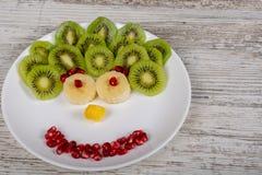 Uma cara feita dos frutos na placa fotos de stock