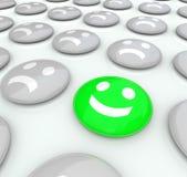 Uma cara feliz entre muitas caras olhando de sobrancelhas franzidas - diferentes Fotografia de Stock Royalty Free