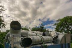 Uma carga das tubulações do ferro abaixo de um céu nebuloso do verão imagem de stock royalty free