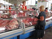 Uma carne de compra da mulher para a venda no mercado de Komarovsky, Minsk Bielorrússia fotografia de stock