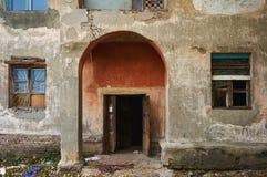 Uma casa abandonada velha com janelas e quebras quebradas na parede Fotos de Stock Royalty Free