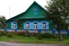 Uma casa bem conservado e bonita em uma vila e uma cama de flor de flores ao lado dela Fotografia de Stock Royalty Free