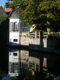 Uma casa branca e uma parede de tijolo refletiram em um canal Imagens de Stock
