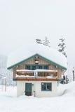 Uma casa coberta com a neve grossa no dia nevado Imagens de Stock