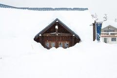 Uma casa coberta com a neve grossa no dia nevado Imagem de Stock Royalty Free