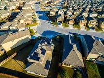 Uma casa com os painéis solares em casas suburbanas do por do sol do telhado ao norte de Austin perto da rocha redonda imagens de stock