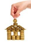 Uma casa construída das moedas isoladas Foto de Stock Royalty Free