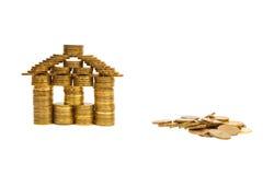 Uma casa construída das moedas isoladas Imagens de Stock Royalty Free