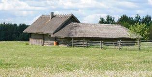 Uma casa da vila com construções de exploração agrícola está na borda da vila pela floresta em torno da casa é um prado com dente imagem de stock