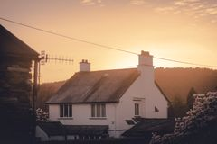 Uma casa de campo inglesa cobrida com sapê confortável com o sol alaranjado morno que ajusta-se atrás dele no meio da mola fotografia de stock
