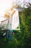 Uma casa de campo pequena com uma mansarda Campo do ver?o fotos de stock royalty free