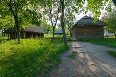 Uma casa de madeira com um telhado cobrido com sapê e um estábulo com feixes e ramos Simples e prático fotos de stock royalty free