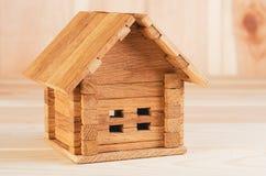 Uma casa de madeira da dobradura do brinquedo disparou em grande em um fundo de madeira fotos de stock