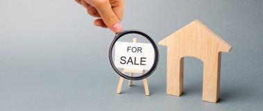 Uma casa de madeira diminuta e um cartaz com a palavra para a venda O conceito de vender uma casa ou um apartamento Propriedade p imagem de stock