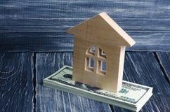 Uma casa de madeira está em uma pilha de cédulas da dor O conceito de comprar e de vender o immovability, aluguel dos apartamento imagens de stock