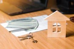 Uma casa de madeira pequena está na tabela junto com um contrato com uma pena, dólares do dinheiro e chaves do apartamento imagens de stock