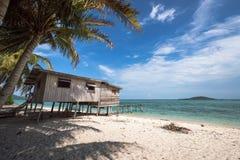 Uma casa de madeira que enfrenta o oceano com o céu azul no fundo Imagem de Stock