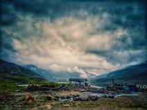 Uma casa entre montes com nuvens azuis Paisagem larga do ângulo imagem de stock