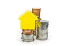 Uma casa modelo e moedas Imagens de Stock Royalty Free