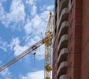 Uma casa nova e um guindaste de construção contra o céu azul foto de stock