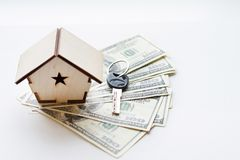 Uma casa pequena encontra-se em um fã de cem notas de dólar As chaves à casa comprada Cópia reduzida da casa fotos de stock