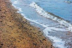 Uma cena do inverno da baía e a linha costeira e as ondas de Sandy no ebbtide Imagem de Stock